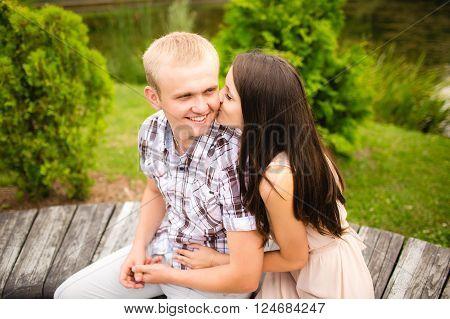 Girl in love kissing happy boyfriend in park on cheek