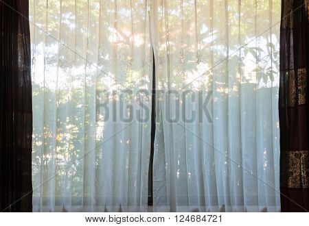 Glass window with a closed translucent curtain