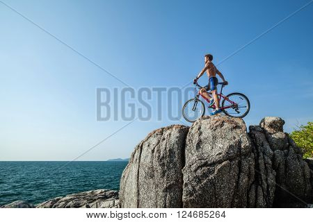 Half-naked sportman standing with bicycle near sea
