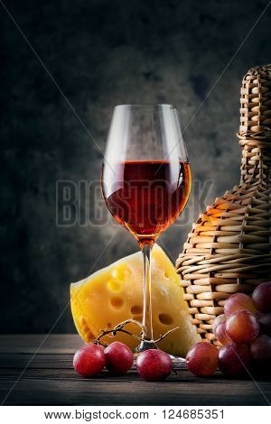 Glass of red wine with grapes and wicker bottle on dark background