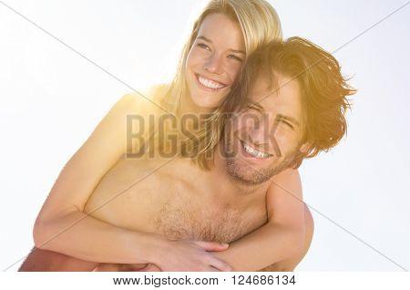 Young couple at beach enjoying summer. Boyfriend piggybacking his girlfriend at beach during honeymoon. Happy young joyful couple having fun in beach.