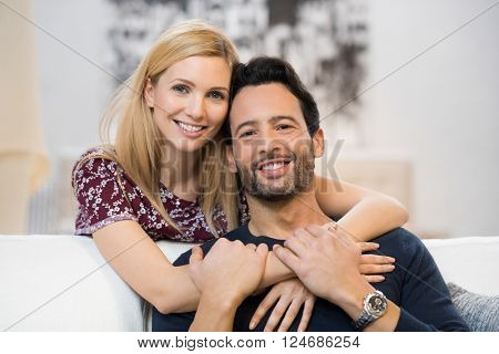 Portrait of a happy embracing couple in casual. Portrait of young woman embracing her boyfriend from behind. Loving young couple sitting on the couch at home and looking at camera.