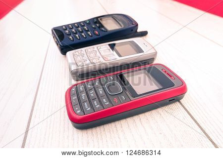 Old mobile phone of different colors lined up in vertical perspective - Cell devices retro technology disposed on wooden panel - Close up cellphones outdated in showcase side view - Old tech display