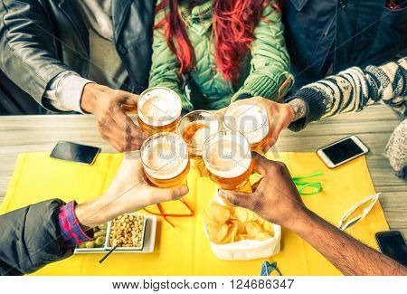 Group of friends cheers with beer cafe interior scene - Multiracial hands holding glasses of Pils in a toast to friendship and happiness -Teenager students gathering in restaurant - Focus on glasses