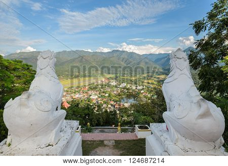 Back view of white lion statue at Wat Phra That Doi Kong Mu with aerial city view of Mae Hong Son against the mountain ranges, Thailand.