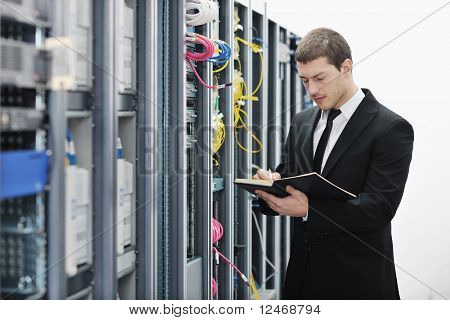 It Businessman Withnotebook In Network Server Room
