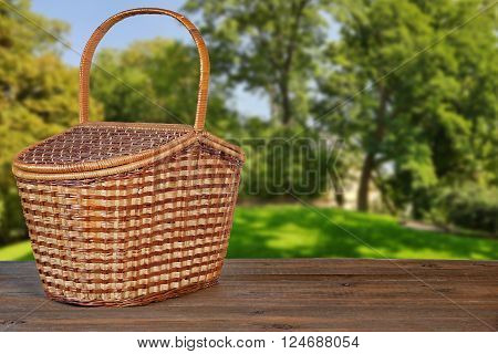 Picnic Basket Or Hamper On  Wooden Bench In Garden