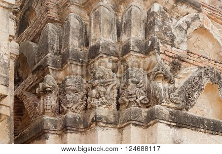 Stone relief handcraft on wall of 12th century temple Wat Si Sawai inside Sukhothai historical park Thailand. UNESCO World Heritage Site.