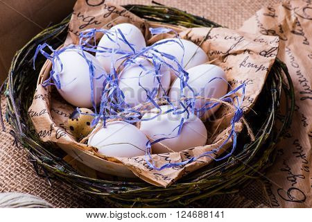 quail and brown eggs in a nest