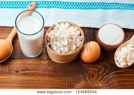 Dairy products on wooden table. Sour cream milk cheese yogurt and eggs.