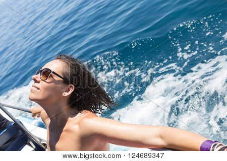 Cheerful woman relaxing and taking tan with eyes closed on edge of boat