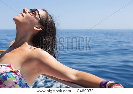 Close-up of smiling woman in sunglasses sunbathing while leaning on shipboard. Copy space area