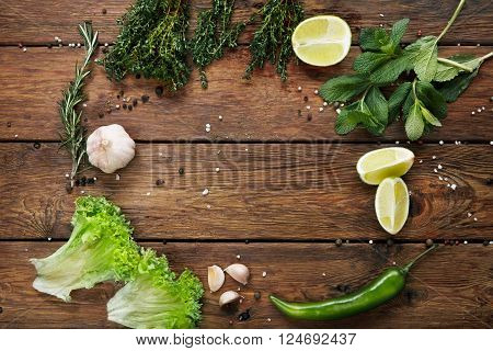 Green fresh food background on rustic wood top view with copyspace. Wood planks and vegetables, cooking ingridients flat lay. Cooking concept, lime, lettuce, garlic, chili pepper, rosemary and mint.