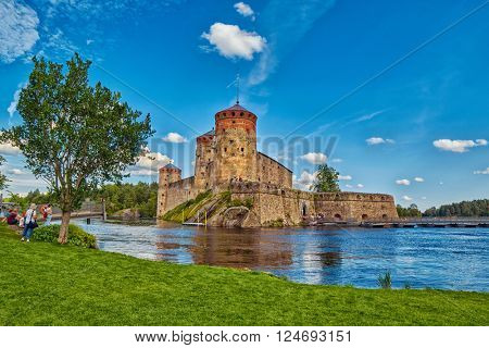 Lake view with grass and reflections of Olavinlinna Olofsborg, the 15th-century medieval three-tower castle located in Savonlinna, Finland.