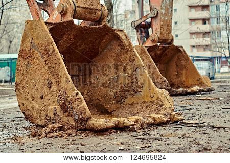 Closeup of the buckets of the excavators standing on the ground