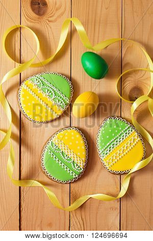Easter homemade gingerbread cookie and yellow end green eggs with ribbon over wooden table. Colorful image top view