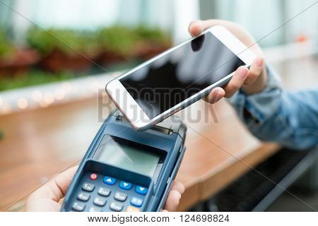 Customer using mobile phone to checkout by NFC technology