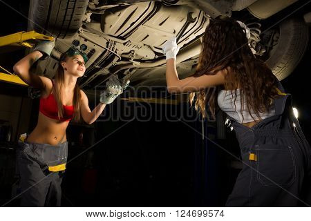 two Beautiful young female mechanic inspecting car in auto repair shop. Sexy mechanic.