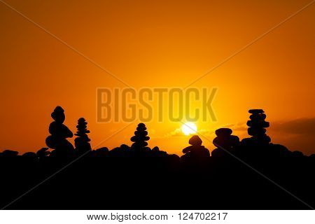 Summer sunset seascape with stone pile stacks silhouettes on tropical island Tenerife, Canary in Spain. Tranquil scene on Playa del Duque.