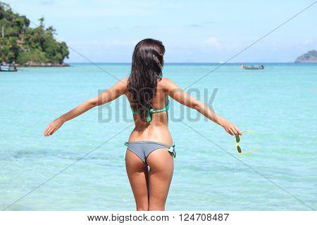 Woman in bikini enjoying tropical beach looking at sea
