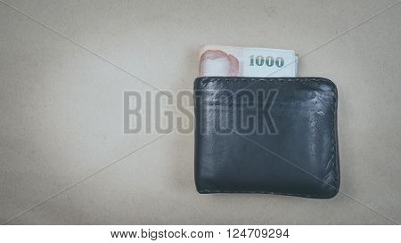 a black leather wallet with Thai baht currency