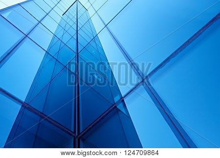 Abstract image of the facade of a modern high rise building covered in reflective plate glass