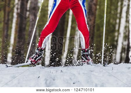Kyshtym Russia - March 26 2016: closeup foot male skier sprays snow from under ski during Championship on cross country skiing