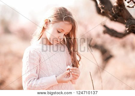 Cute baby girl 4-5 year old holding peach flower in meadow outdoors. Countryside.