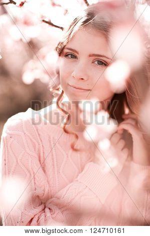 Smiling teen girl posing in peach blooming outdoors. Peach garden. Teenager hood.