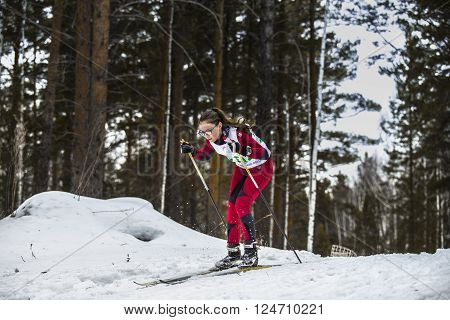 Kyshtym Russia - March 26 2016: young girl skier athlete coming down mountain on skis during Championship on cross country skiing