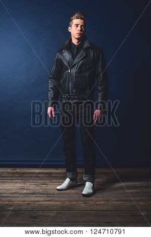 Vintage 1950 fashion man wearing leather jacket and jeans.
