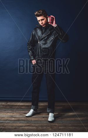 Vintage 1950 Fashion Man Listening To Portable Radio. Wearing Leather Jacket And Jeans.