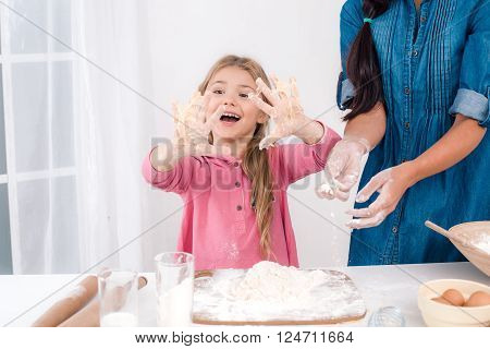 Sweet time of family cooking. Mother and daughter having fun while preparing meal. Nice white interior. Daughter having hands smeared with dough