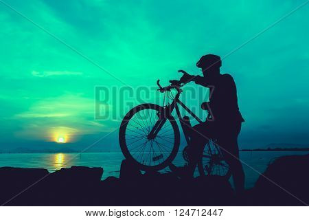 Silhouette of bicyclist standing with bike on a rocky trail at seaside on colorful sunset sky background. Active outdoors lifestyle for healthy concept. Vintage style.