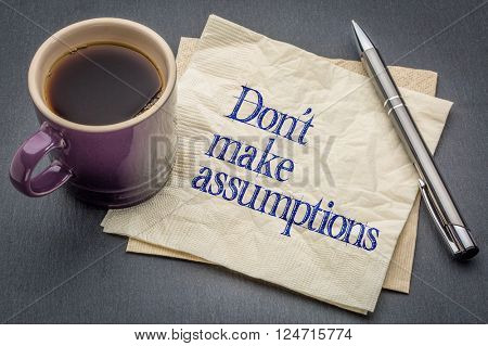 Don not make assumption advice or reminder - handwriting on a napkin with cup of coffee against gray slate stone background