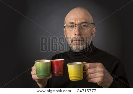 Morning coffee anybody? 60 years old  bald man with a beard and glasses carrying three espresso coffee cups - a headshot against a black background