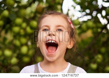 Portrait of a cute little girl making an excited face with her mouth wide open
