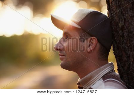Profile shot of a young man looking away meditatively in an early morning forest
