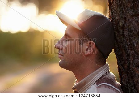 Profile shot of a young man with his eyes closed meditatively in an early morning forest