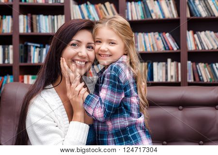 Photo of mother and little daughter. Nice cozy interior with big bookcase. Mother and daughter looking at camera, hugging and smiling