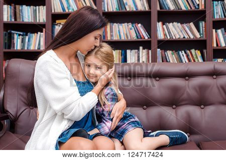 Photo of mother and little daughter. Nice cozy interior with big bookcase. Daughter looking at camera and smiling while mother kissing her