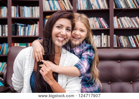 Photo of mother and little daughter. Nice cozy interior with big bookcase. Mother and daughter looking at camera, hugging and cheerfully smiling
