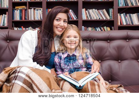 Photo of mother and little daughter. Nice cozy interior with big bookcase. Mother and daughter reading bedtime story, looking at camera and smiling
