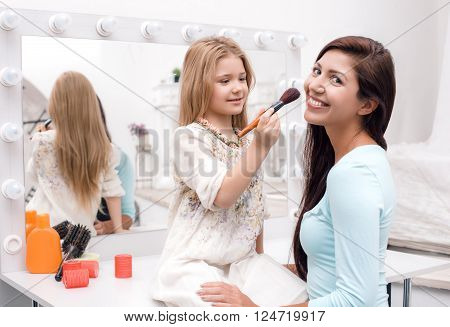 Young beautiful mother and little daughter while applying makeup. Nice cozy bedroom. Daughter helping mother to use brush for makeup
