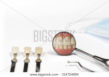 Three teeth attached to metal rods next to dental pick and mirror displaying clenched front teeth besides mask on white table