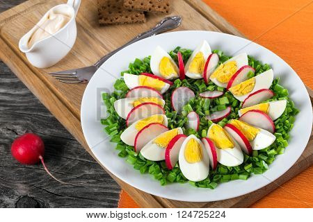 Delicious Spring onion eggs radish salad in a white dish with fork on an cutting board on an old rustic wooden table horizontal close-up top view