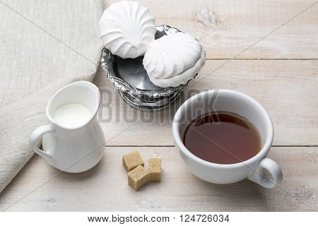 Set of cup black tea and dessert on bright wooden table