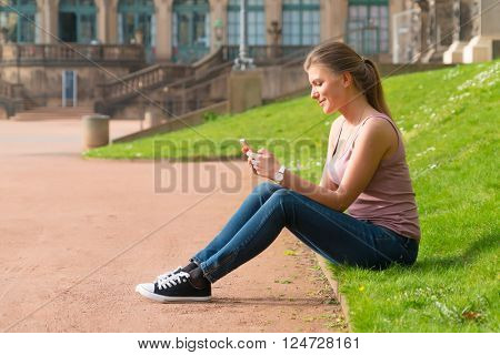 Woman tourist reads the information in the smartphone at the Zwinger palace, Dresden, Germany