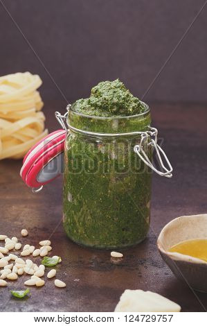 Basil pesto with pine nuts. Homemade basil pesto in a flip top jar, ingredients and pasta. Macro, selective focus, vintage toned image, blank space