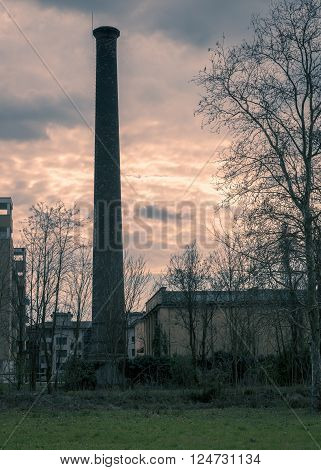 In the picture a large chimney located close to homes split toning color used.